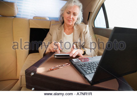Senior businesswoman with briefcase sitting in back seat of car using personal electronic organiser and laptop - Stock Photo