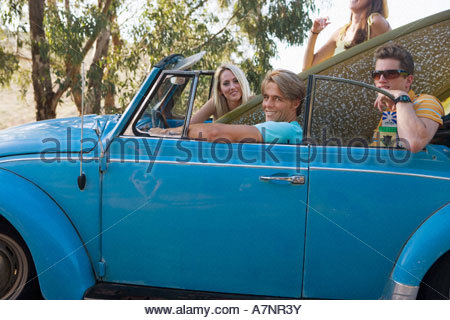 Four teenagers 17 19 sitting in blue convertible car with surfboard portrait side view - Stock Photo