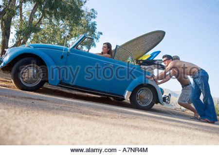 Two teenage boys 17 19 pushing car teenage girl steering side view surface level tilt - Stock Photo
