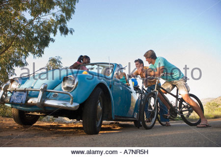 Group of friends talking at roadside teenage boys 17 19 on bicycles teenage girls in blue car - Stock Photo