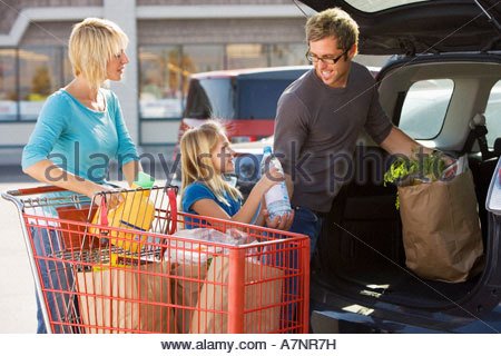 Family loading car boot with groceries in supermarket car park smiling side view - Stock Photo