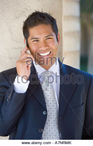 Businessman using mobile phone smiling close up front view portrait - Stock Photo