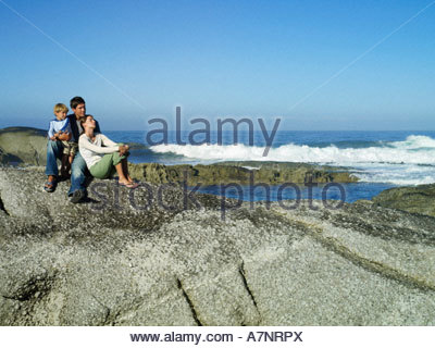 Family sitting on rocky beach looking at Atlantic Ocean boy 4 6 in father s lap woman leaning against man - Stock Photo