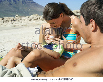 Family relaxing on beach boy 4 6 sitting in mother s lap woman applying suncream to son s face side view - Stock Photo