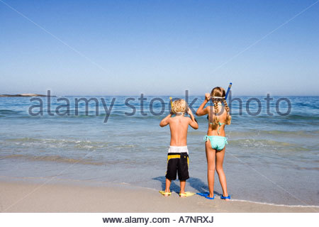 Boy 4 6 and girl 5 7 standing side by side on sandy beach at water s edge wearing snorkels rear view - Stock Photo