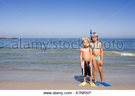Boy 4 6 and girl 5 7 standing side by side on sandy beach wearing snorkels and flippers front view portrait - Stock Photo