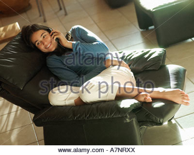 Teenage girl 17 19 reclining on leather armchair at home using mobile phone smiling side view - Stock Photo