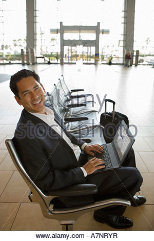 Businessman waiting in airport departure lounge using laptop smiling side view portrait - Stock Photo