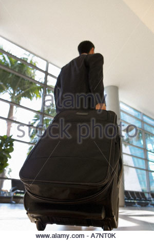 Businessman walking in airport terminal with luggage in tow rear view surface level - Stock Photo