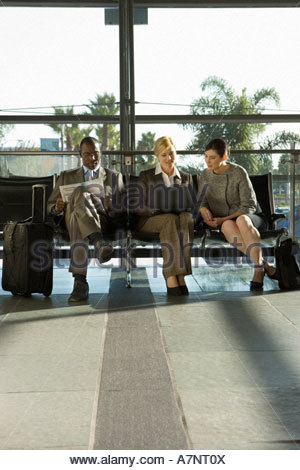 Three business people sitting in airport departure lounge businesswoman and colleague using laptop front view - Stock Photo