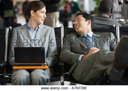 Two business people sitting in airport terminal woman using laptop man resting with feet up on luggage talking - Stock Photo