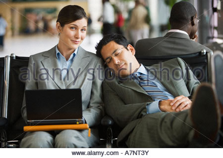 Two business people sitting in airport terminal tired man resting head against woman s shoulder woman using laptop - Stock Photo