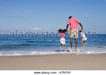 Father and two children 5 7 playing in Atlantic surf on sandy beach jumping up rear view - Stock Photo