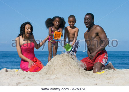 Family building sandcastle on beach children 5 7 pouring sea water onto sand smiling front view - Stock Photo