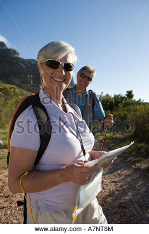 Mature couple hiking on mountain trail woman standing in foreground holding map smiling portrait - Stock Photo