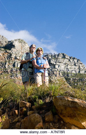 Mature couple hiking on mountain trail looking at scenery smiling low angle view - Stock Photo