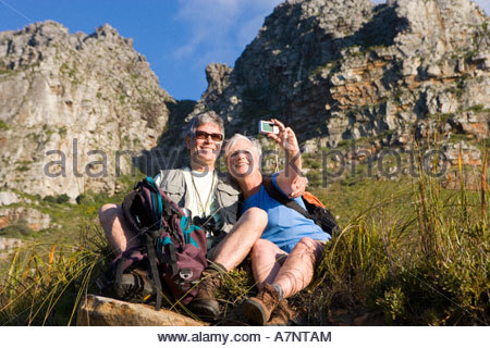Mature couple sitting on mountain slope woman taking self portrait with digital camera smiling low angle view - Stock Photo