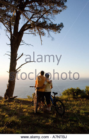 Mature couple standing with bicycles on mountain trail looking at Atlantic Ocean horizon rear view - Stock Photo