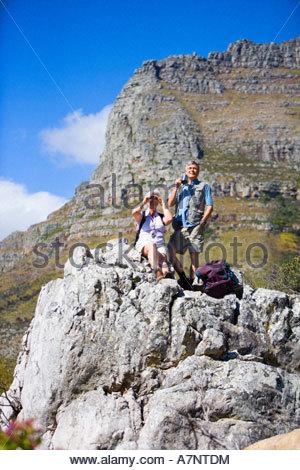 Mature hikers resting on rock in mountains woman looking at scenery through binoculars man holding mug - Stock Photo