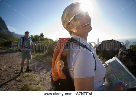 Mature couple with rucksacks hiking on mountain trail in bright sunlight focus on woman holding map smiling lens - Stock Photo
