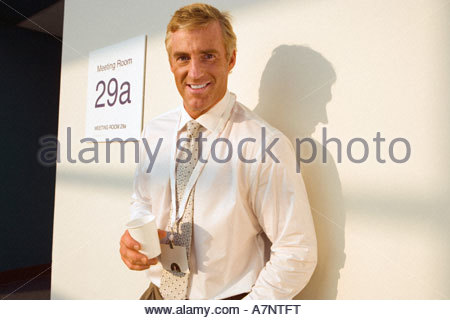 Businessman standing outside meeting room taking coffee break casting shadow on wall smiling portrait - Stock Photo