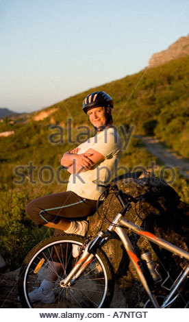 Mature woman taking break from cycling on mountain trail standing beside rock arms folded side view portrait - Stock Photo