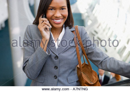 Businesswoman with handbag standing on escalator using mobile phone smiling front view portrait elevated view - Stock Photo