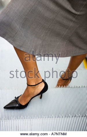 Businesswoman in grey skirt and high heels standing on escalator close up low section - Stock Photo