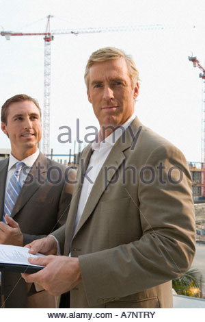 Two businessmen standing outdoors mature man holding document smiling portrait - Stock Photo