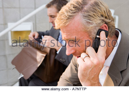 Two businessmen sitting on steps man looking in briefcase focus on mature man using mobile phone side view - Stock Photo