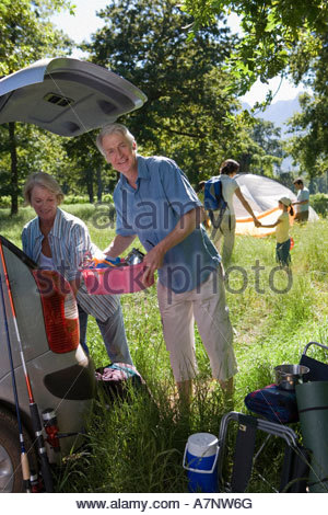 Multi generational family unloading car on camping trip focus on grandparents beside car boot smiling portrait - Stock Photo