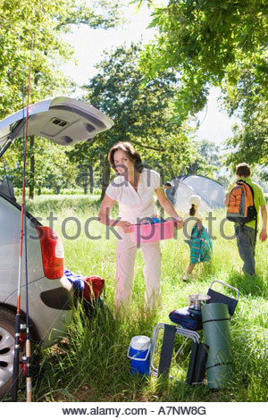Family unloading car on camping trip focus on woman holding pink container beside car boot smiling portrait - Stock Photo