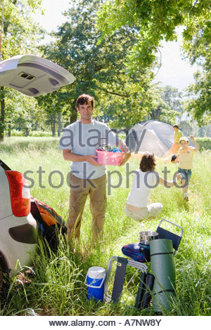 Family unloading car on camping trip focus on man holding pink container beside car boot smiling portrait - Stock Photo