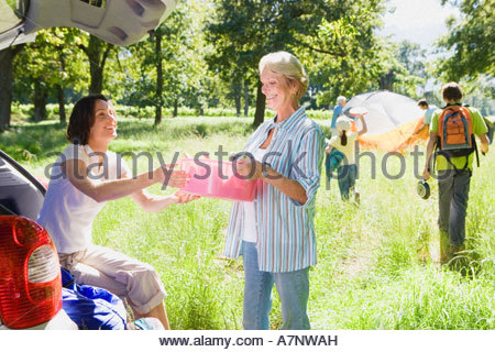 Multi generational family unloading car on camping trip adult daughter passing mother container from car boot - Stock Photo