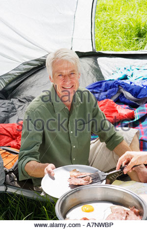 Person serving senior man fried breakfast on camping trip man sitting inside tent smiling portrait - Stock Photo