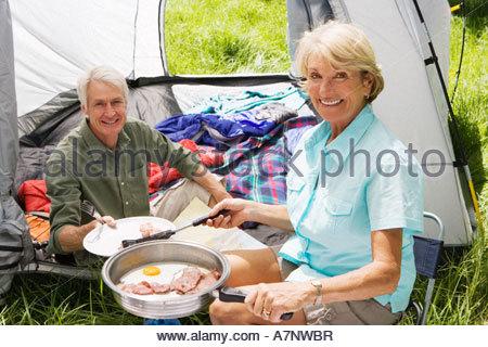 Senior woman serving husband fried breakfast on camping trip man sitting inside tent smiling portrait - Stock Photo