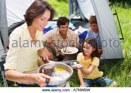 Family eating fried breakfast on camping trip woman serving bacon to daughter 8 10 beside tent - Stock Photo