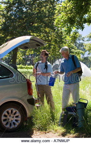 Senior man and adult son unloading parked car on camping trip in woodland clearing side view - Stock Photo