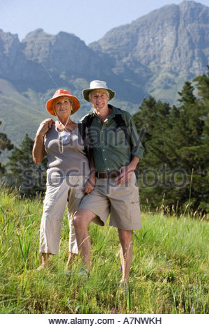 Senior hikers with rucksacks and sun hats standing on mountainside arms around each other smiling portrait - Stock Photo