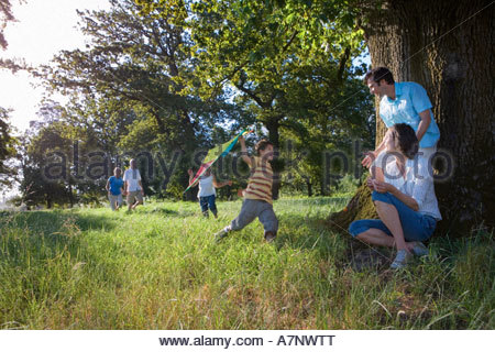 Multi generational family exploring woodland clearing parents resting beside tree boy 8 10 playing with kite - Stock Photo