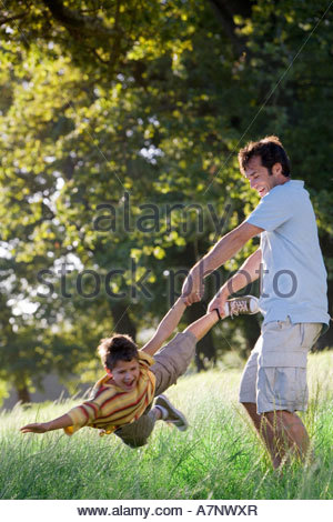 Father swinging son 8 10 in woodland clearing boy shouting side view tilt - Stock Photo