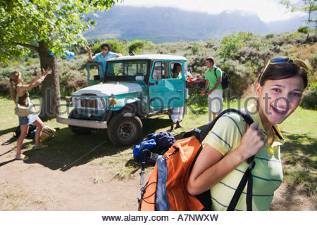 Group of young adults departing on hiking trip man unloading jeep focus on woman in foreground smiling - Stock Photo