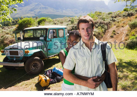 Young couple standing near parked jeep at start of camping holiday woman embracing man smiling portrait - Stock Photo