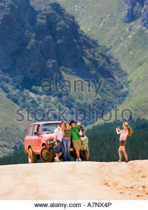Young woman photographing four friends standing beside parked jeep on dirt track in mountain valley - Stock Photo