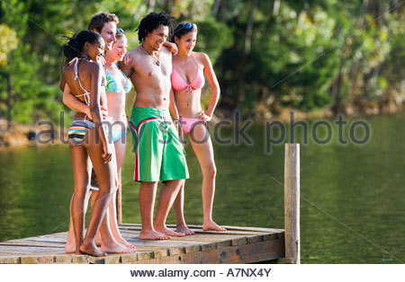 Five young adults in swimwear standing side by side on lake jetty smiling side view - Stock Photo