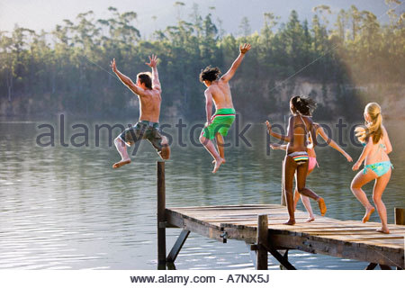 Five young adults in swimwear jumping from jetty into lake rear view - Stock Photo