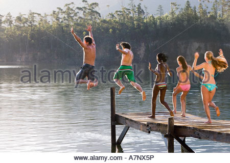 Five young adults in swimwear jumping side by side from jetty into lake rear view - Stock Photo