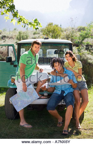 Young woman and two male friends leaning against parked jeep consulting road map smiling portrait - Stock Photo
