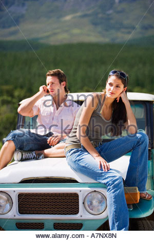 Young couple sitting on bonnet of parked jeep in mountain valley man using mobile phone - Stock Photo