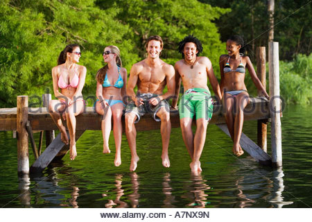 Five young friends in swimwear sitting side by side on lake jetty front view smiling portrait - Stock Photo